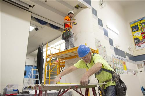 Drywall installers work at Bear Valley Elementary