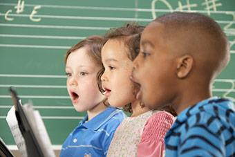 Children singing from sheet music.