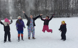 students playing in the field of snow