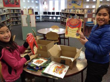 children in library holding up books