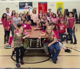 Students and principal in cafeteria wearing pink