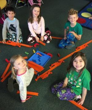 Students on classroom floor with road building toys