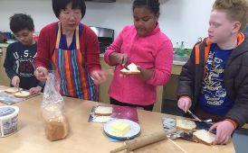 Students helping stir a mixing bowl