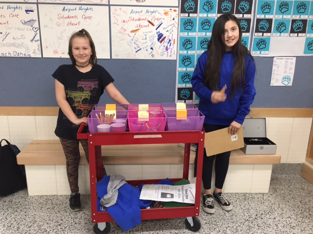 Two girls standing next to a sales cart of school supplies.