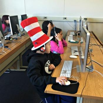 Boy wearing a Cat in the Hat Cap working on a computer