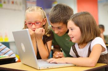 Elementary Students looking at a laptop.
