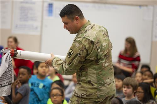 A member of the National guard holds a large fake cigarette during an assembly at Muldoon Elementary.