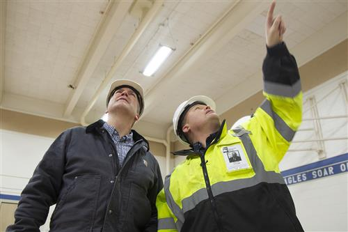 nt of the structural damage to Sen. Dan Sullivan at Eagle River ElemTom Fenoseff, right, explains the exteentary.