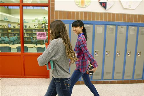 A student host walks with an exchange student from Chitose, Japan in the hallway at Mears Middle School.