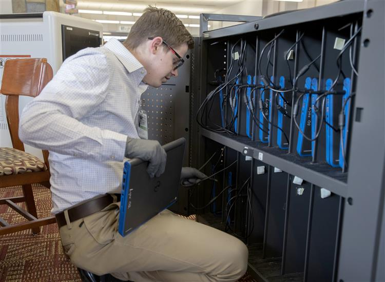 An IT Employee works on computers at East High School.