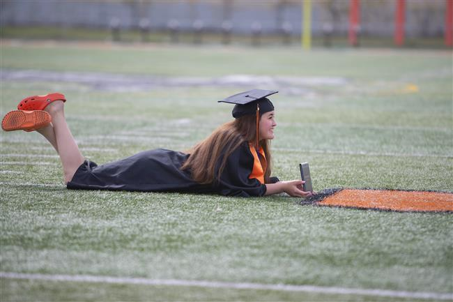 A West High graduate poses for a photograph on the West High footbal field Monday, May 18, 2020. (Robert DeBerry/ASD)