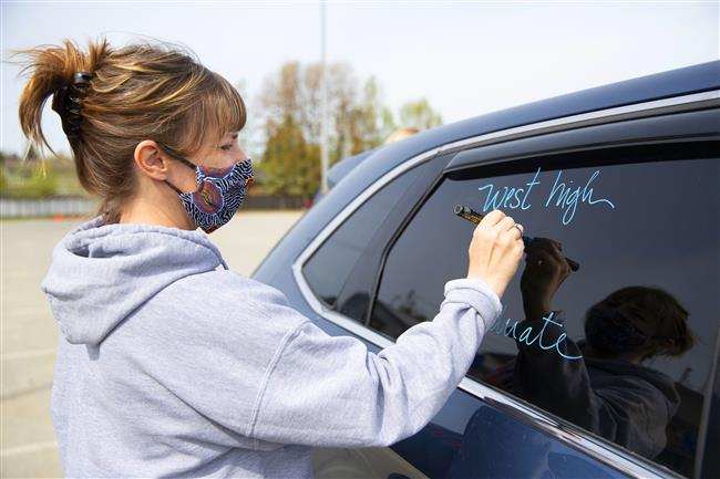A West High School staff member decorates a car window during Monday's graduation ceremonies. (Robert DeBerry/ASD)