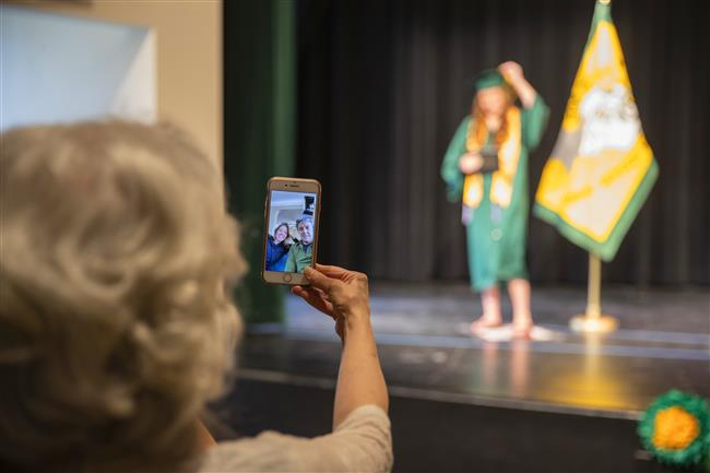Family members watch in the little theater at Service High School as they Facetime with other family members as a Service Hig