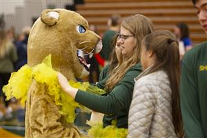 Students helping prepare the mascot for the assembly