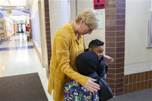 A Denali Montessori teacher hugs returning students on the first day of school.