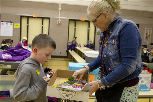Beverly Hardesty, Certified Behavior Interventionist/Title I Teacher, helps Rylan pick out a prize after winning a raffle