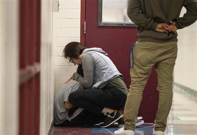 K-6 special education teacher Katherine Fox comforts a student in the hallway at Whaley School. (Robert DeBerry/ASD)
