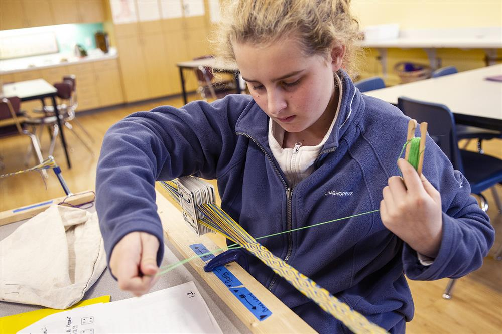 A student works on a Tablet Weaving project at Winterberry Charter School.