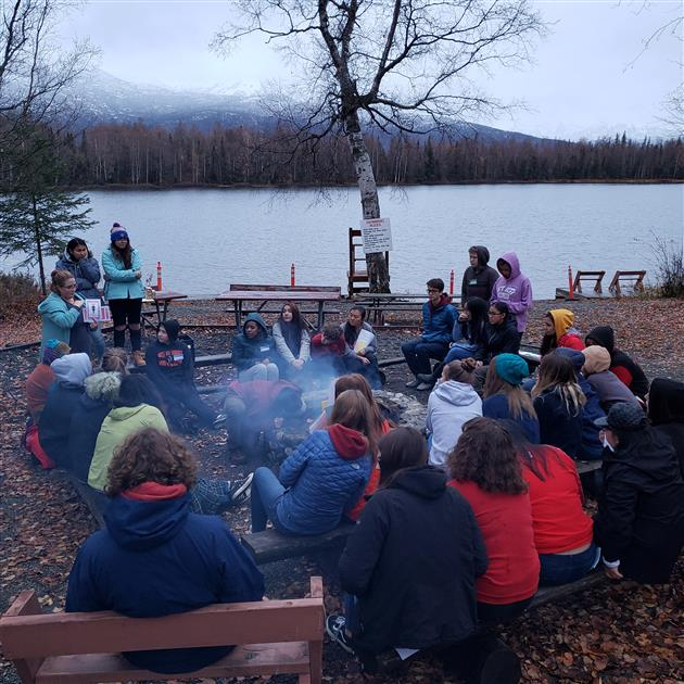 ASD French students and teachers gather around the campfire at French Camp