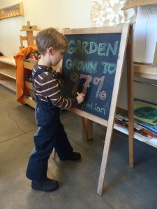 Boy drawing on chalkboard.