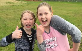 Two smiling students face the camera and give thumbs up