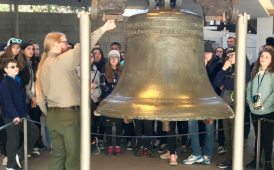 Romig students stand around Liberty Bell with tour guide