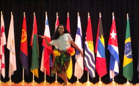 a Romig student dances on stage in front of world flags