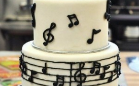 tiered cake decorated with musical note frosting