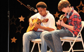 two boys play guitar in a talent show