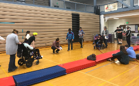 students in wheel chairs play blind soccer