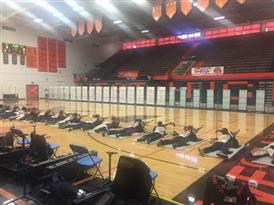 Rifle Team laying on floor in gym shooting at targets