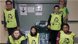 West High green team students pose by recycling bins
