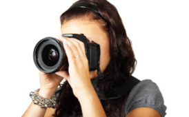 female taking photo with a large lens camera