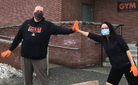 gloved teachers wear face masks and give a high five